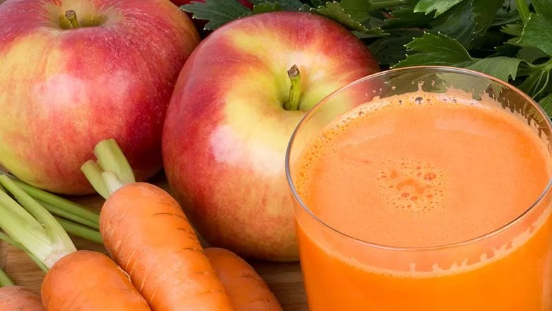 orange colored juice on a timber table next to whole red apples, carrots with the tops on but trimmed, and celery leaves
