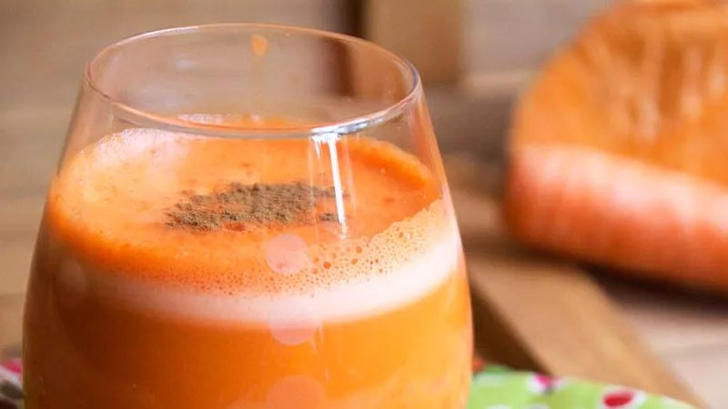 sweet potato and pear juice in a glass on a bench next to a chopped sweet potato on a timber chopping board