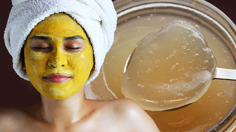 How to Make Your Own Sea Moss Face Mask - woman with turmeric mask and a white towel wrapped around her head like in a spa, with a jar of sea moss gel in the background