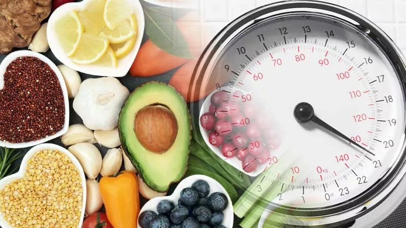 12 Tips for Losing Weight Fast at Home. Scales and a spread of whole foods on a stone bench top including avocado, cranberries, lemon, capsicum, carrot, garlic, bay leaves, ginger, lentils and tomato