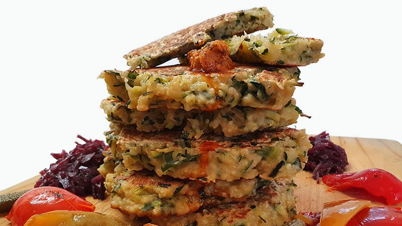 feature-cooked-and-served-zucchini-fritters-with-sea-moss-on-a-timber-chopping-board