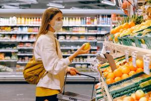 woman-in-yellow-tshirt-and-beige-jacket-holding-a-fruit-