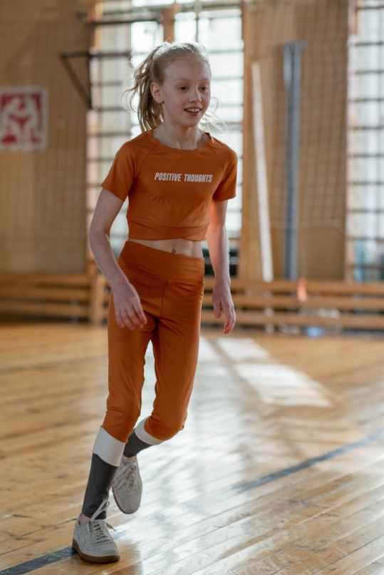 woman in orange sports wear standing in wooden floor