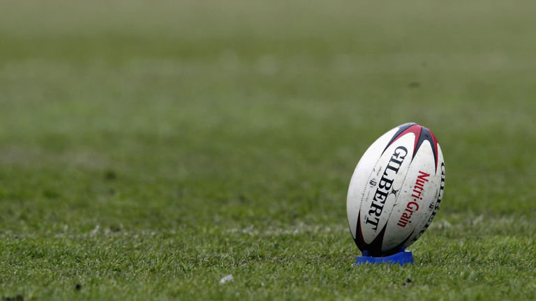 A professional picture of a rugby ball placed on a field