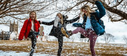 Des femmes qui portent des manteaux jouent dans la neige.