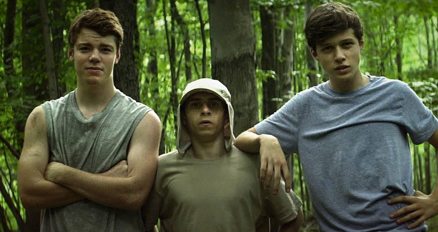 the Kings of Summer still of three teenage boys wearing tshirts in forest