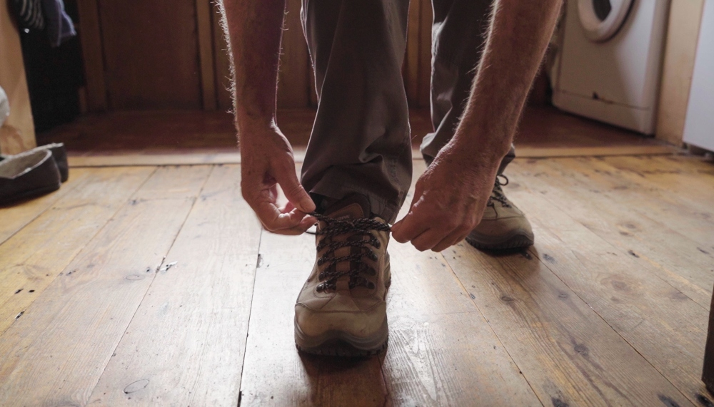 a person crouching to tie a shoe-lace a still from Walks of Life Andy Thatcher