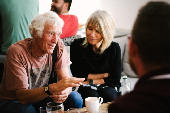 Cinematographer Roger Deakins is sat next to a woman talking to people at Plymouth College of Art