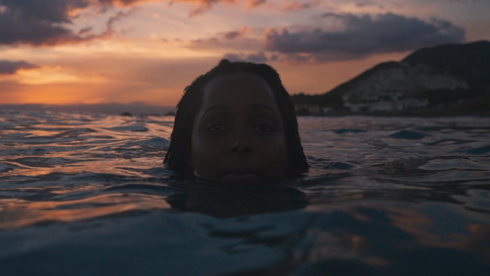 Still of Surf Girls Jamaica: The Right To Roam. A woman is in the sea, submerged with just her head showing above the water-line