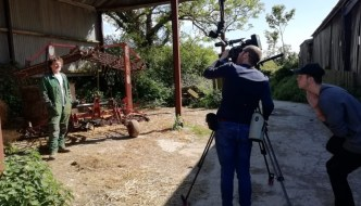 a farmer is being interviewed and filmed by James Cox