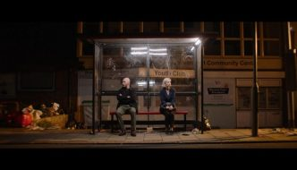 still from Bus Stop by Vanessa Bailley. Two people a man and a woman sit in a bus stop at night. The area looks pretty run down