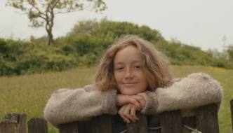 a girl in a jumper has her arms crossed on a fence with her chin resting on it as she looks at the camera with a green field behind