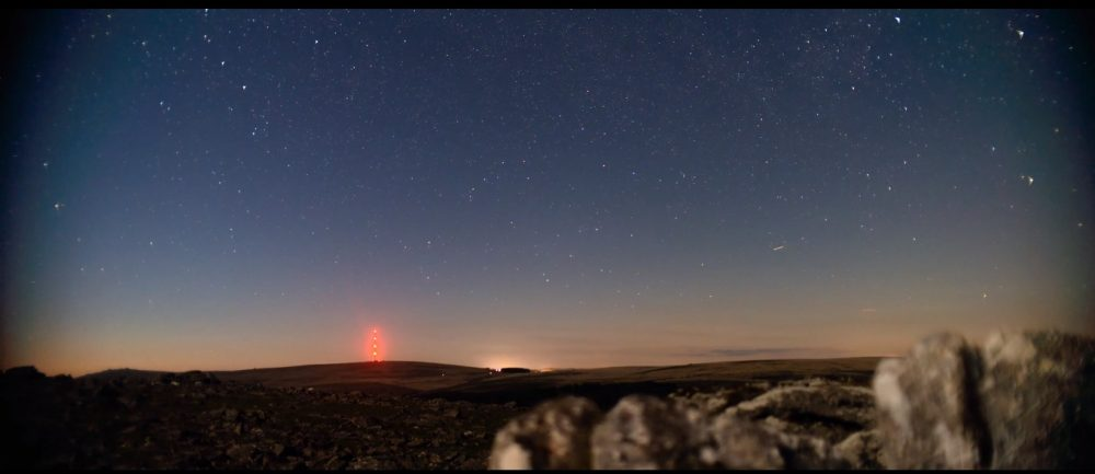 an image from dartmoor to the night sky as it gets darker. There are rocks in the fore ground and the line between dusk and night at the horizon with it getting darker and showing stars