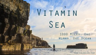 a poster for the Vitamin Sea film. The words are on an image of a woman standing up on a paddleboard in the distance on the sea with dark cliffs towering over her