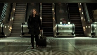 a woman is pulling a suitcase with a bank of escalators behind her