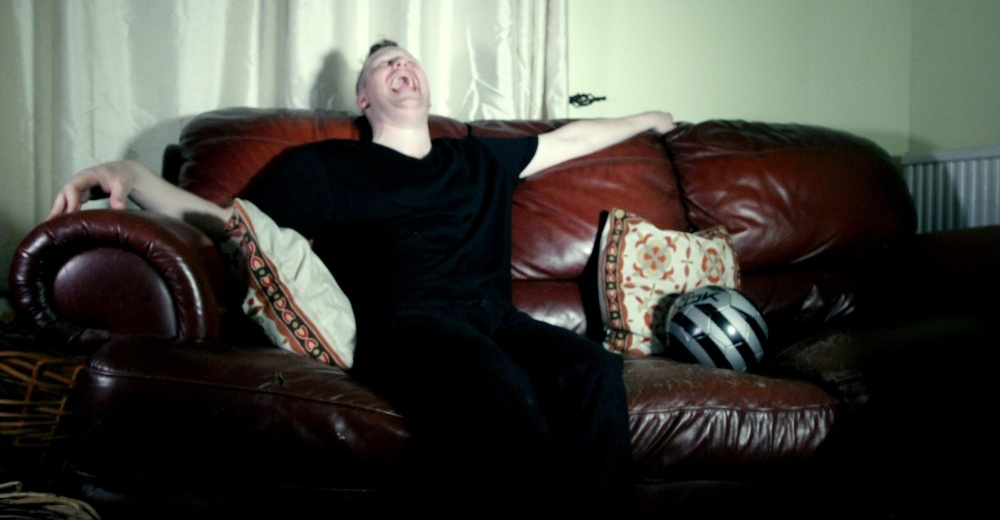 a man is learning back laughing sitting on a sofa next to a silver football