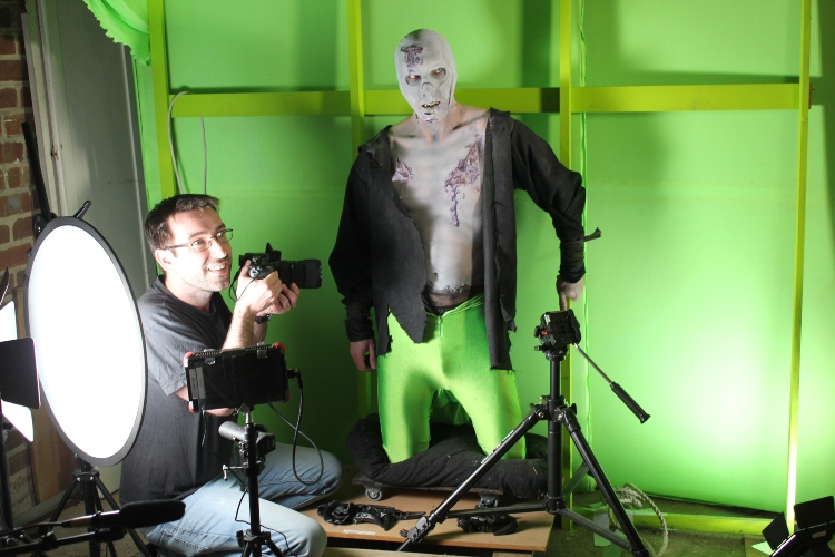 a green screen with a man dressed up and someone with a camera
