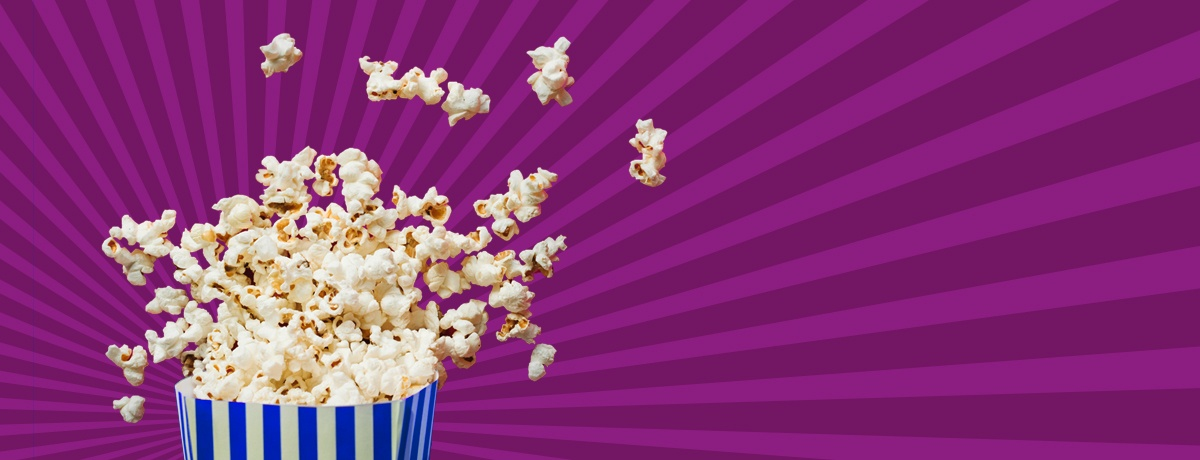 popcorn bursting out of the back with a purple background