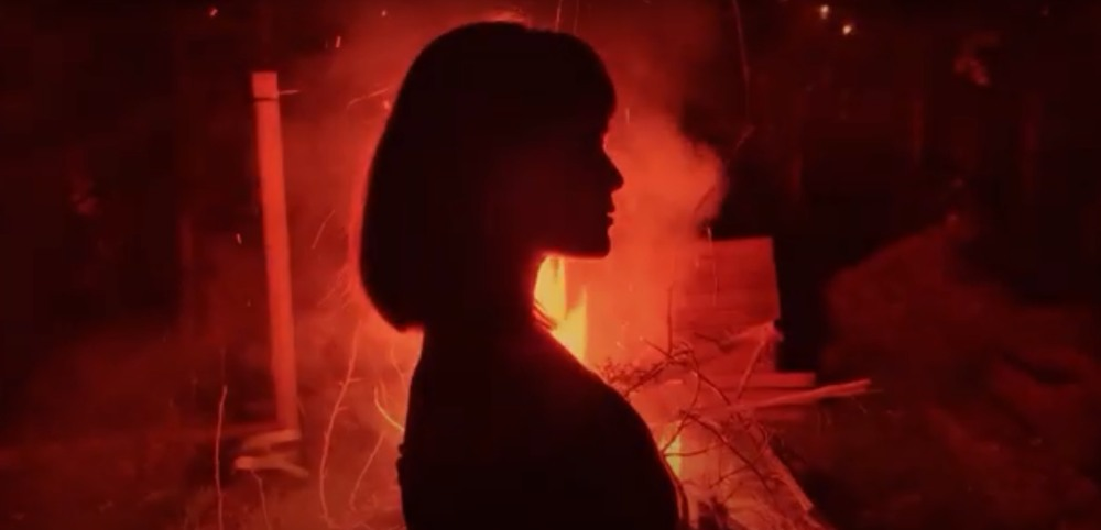 still from the Booshka video for Pyro, silhouette of a woman with a fire behind