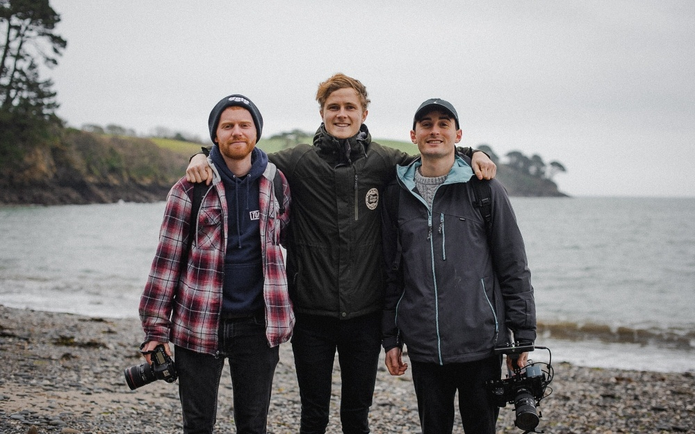 three young men holding cameras on a beach together
