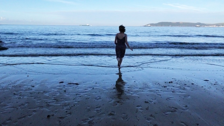 a still from a summer of birds - a woman running into the sea on a sandy beach