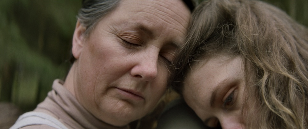 still from Wake: two heads - an older woman and a younger woman - leaning on each other