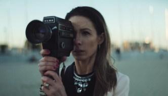 a woman behind a super 8 camera