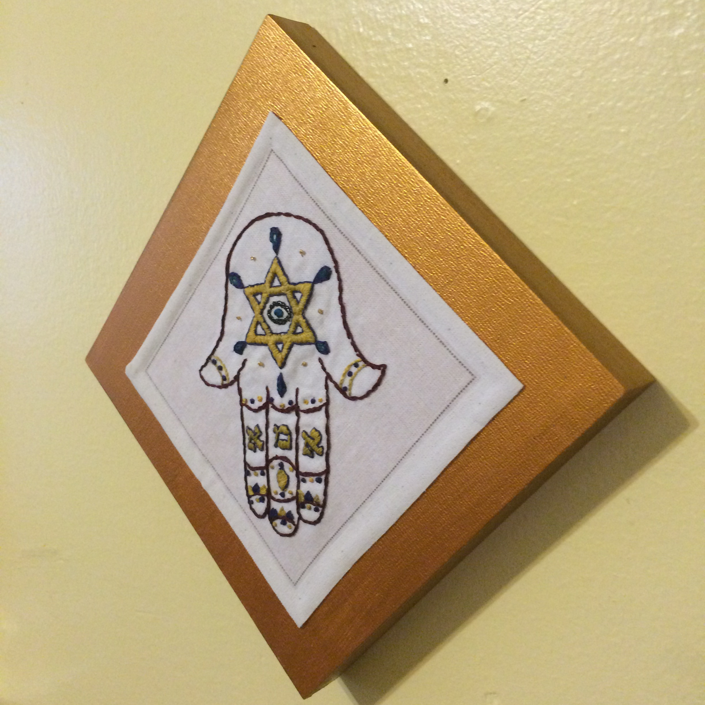 Hand embroidered hamsa amulet mounted on wood tile.