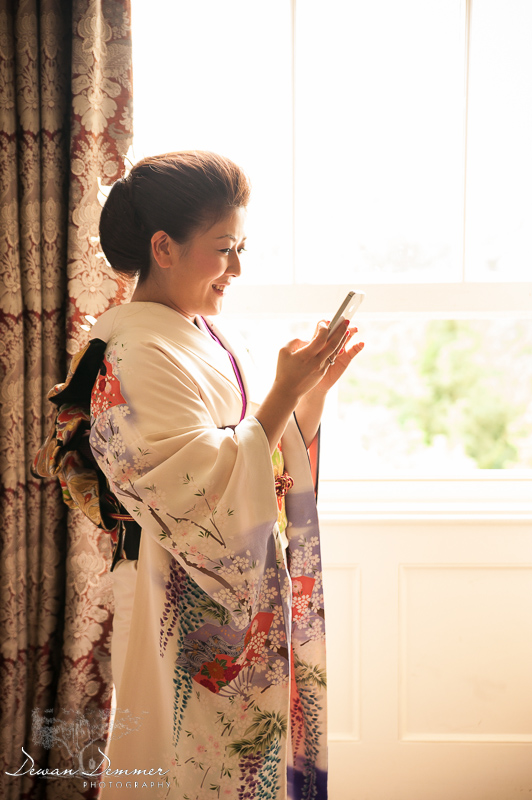 Bride reading text messages by window