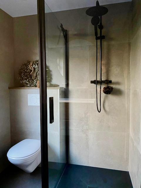 Glazen douchewand landelijke badkamer beige tegels zwarte douchestand krans