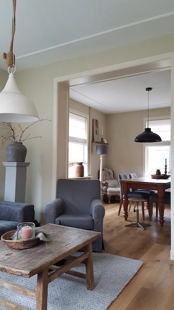 Landelijke salontafel fauteuil met grijze hoes kruik op zuil ombouw doorgang kamer keuken
