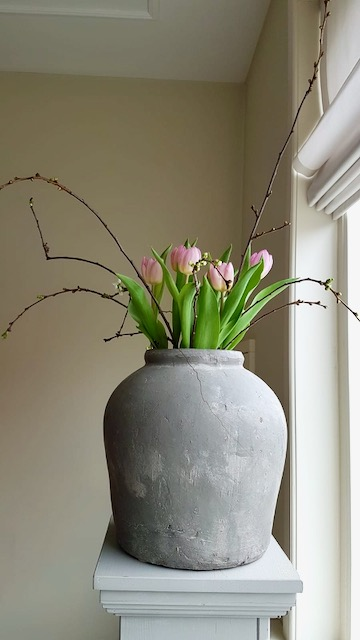 Zuil met landelijke kruik met roze tulpen