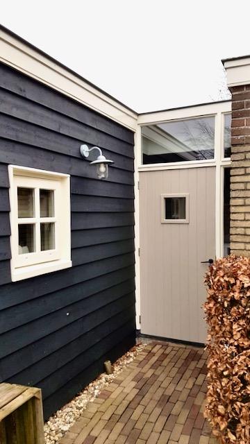 Gepotdekselde schuur zwart taupe achterdeur buitenlamp landelijk