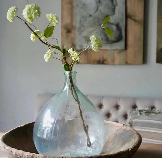 Houten olijfbak met glazen fles en kunstbloem ornament muur eetbank landelijk