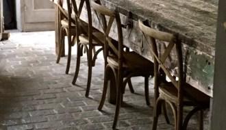 Lange eettafel met houten stoelen RAW stones vloer