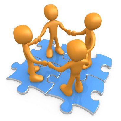A cartoon of four people holding hands on puzzle pieces.