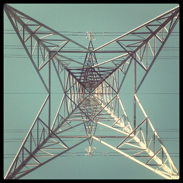 Looking up at an electricity pylon.