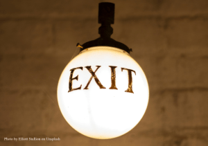 light with exit words on it represents business exit strategy