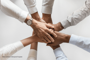 leadership team hands huddle to begin merger