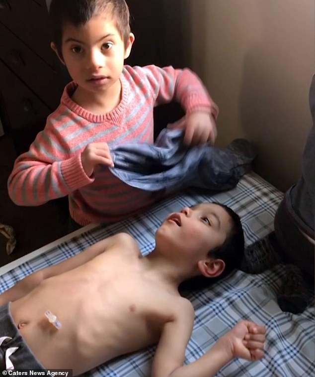 Simon Clark is just four-years-old, yet helps his PE teacher father Jeremy, 33, and nurse mother Nicole, 31, from Utah, feed and dress adopted brothers. He is seen dressingJon, six, who has Cerebral Palsy