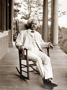 Mark Twain sitting in a rocking chair on a porch, April 1 – Celebrate Your Inner Fool