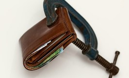 Image of a wallet in a vice as a means to financial peace.