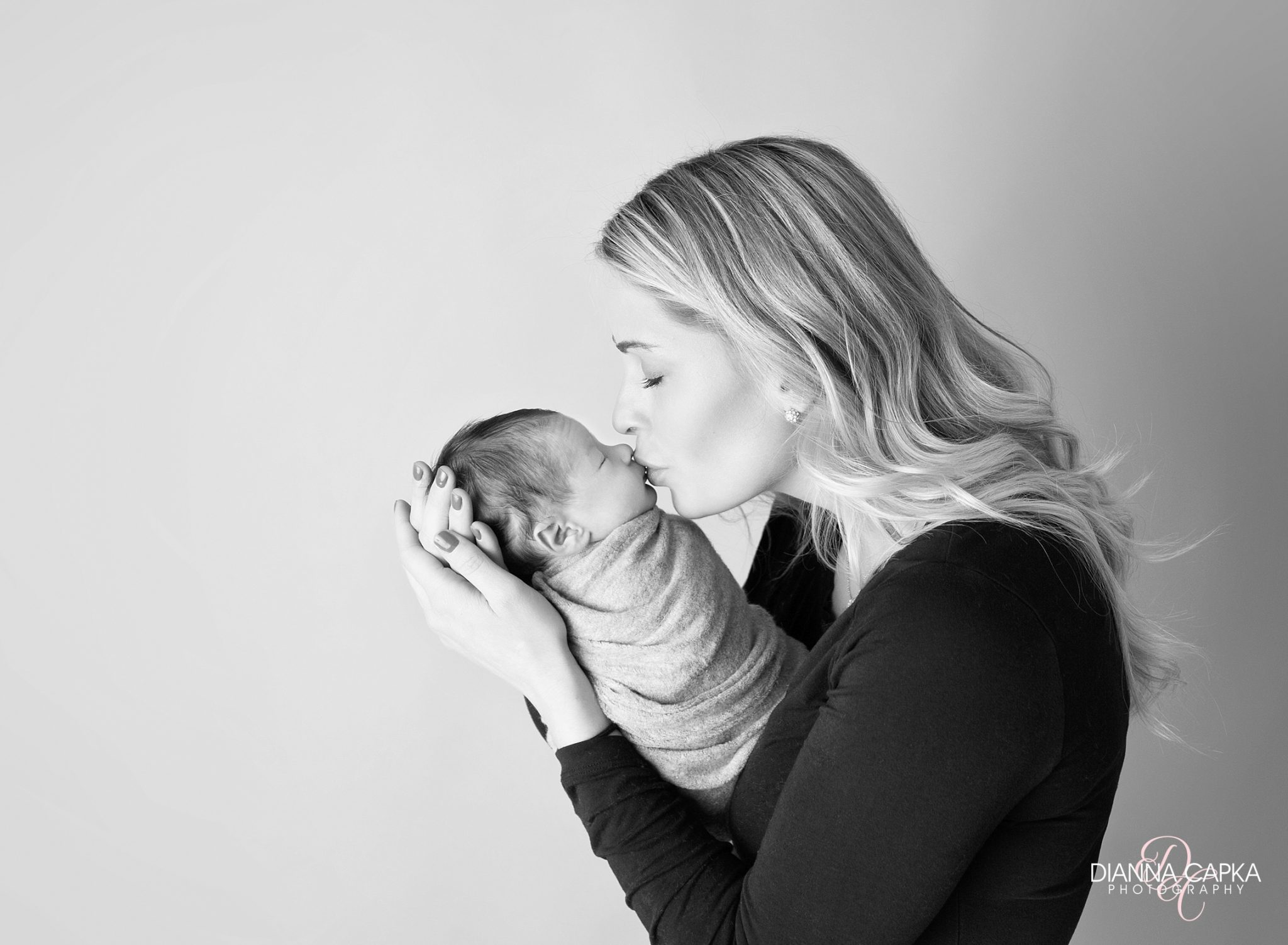 Newborn Photographer Lancaster newborn with mom in black wrapped on gray seamless in black and white