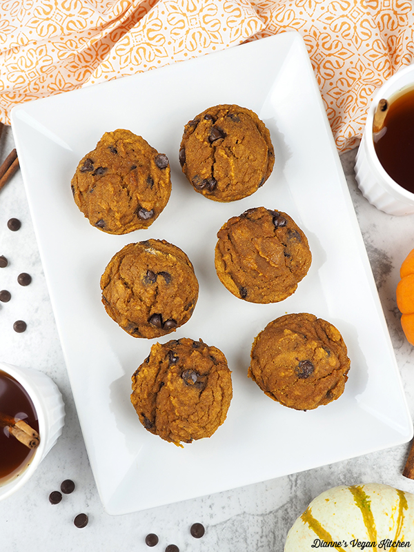 Vegan Chocolate Chip Pumpkin Muffins on platter with tea and pumpkins