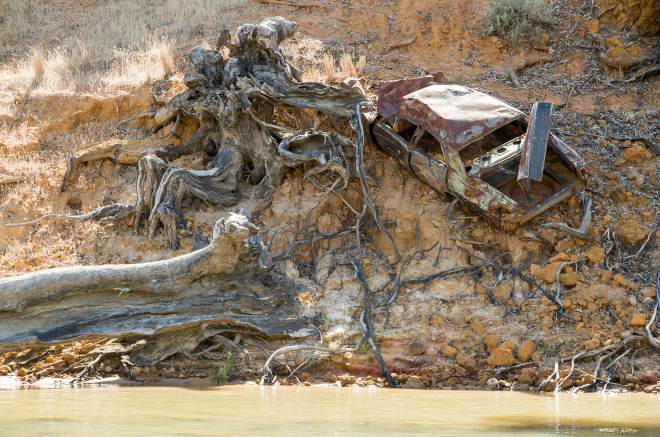 Rusty car off a cliff on the Murray River bank