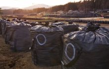 Bags filled with contaminated waste sit in a field in the village of Iitate, Fukushima Prefecture, in March 2016. | KYODO