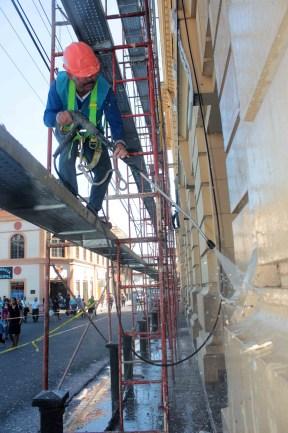 Un trabajador de la comuna capitalina limpia las paredes del Teatro Nacional. Foto Diario Co Latino/ Guillermo Martínez