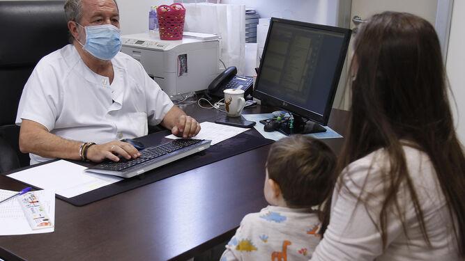 El veterano pediatra atiende a una madre y a su hijo.