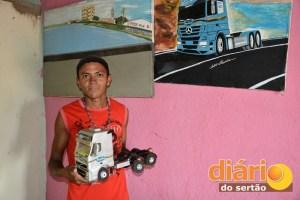 Maurício com uma réplica de caminhão. Na parede, uma pintura do Leblon de Cajazeiras e de um caminhão na estrada