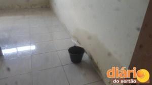 Os funcionários espalham baldes para pegar água